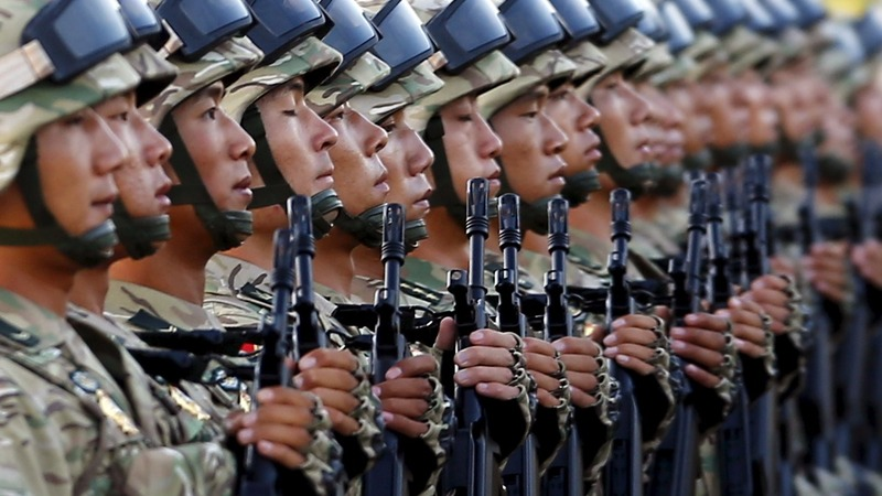 China rolls out new weapons but will cut troops