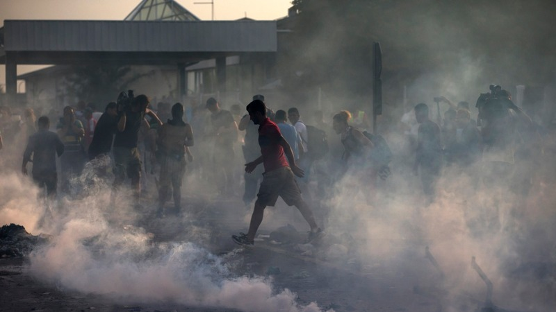 Migrants face water cannon, tear gas