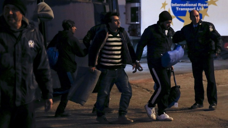 Migrants escorted from Lesbos in cuffs