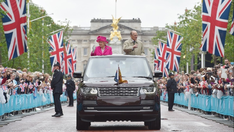 INSIGHT: Partygoers brave rain for Queen's birthday