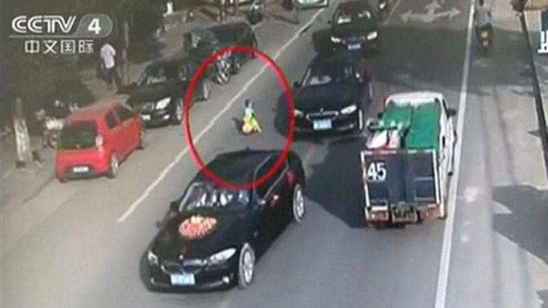 INSIGHT: Chinese boy rides toy car into traffic