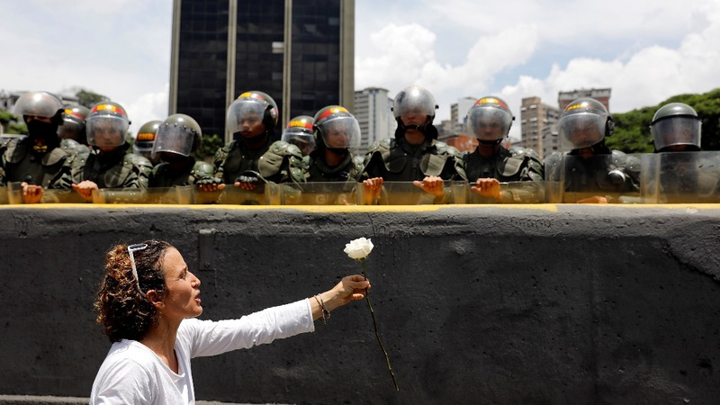 Roses in hand, Venezuelan women face security forces