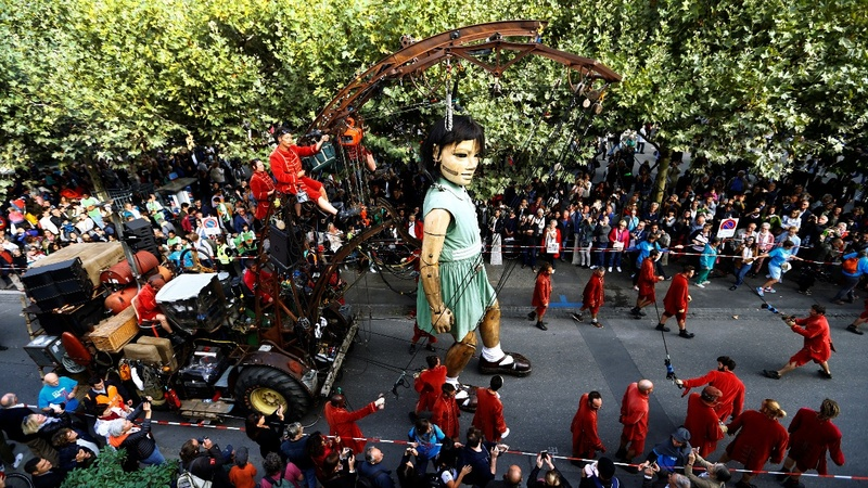 INSIGHT: Giant puppets walk Geneva streets
