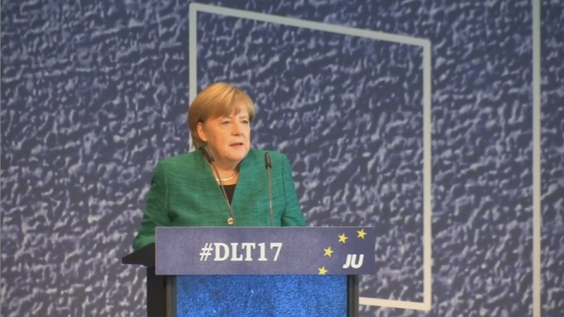 Merkel settles migrant spat with allies to pursue coalition